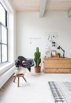 Un salon cosy avec la chaise à. Acculé de Eames, un tapis style berbère et un chouette cactus