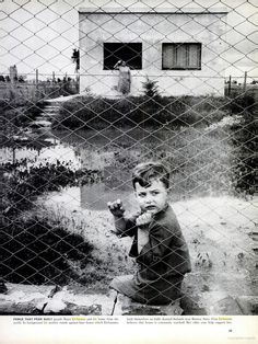 Fence That Fear Built guards Haasi Eichmann and his home from the world. In background his mother stands against bare house which Eichmanns built themselves on badly drained flatlands near Buenos Aires. Frau Eichmann believes that house is constantly watched. Her older sons help support her.