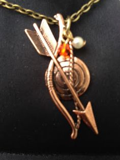 One of the latest Hunger Games Mockingjay Necklace with the Bow and Arrow symbol along with the pearl and gem.
