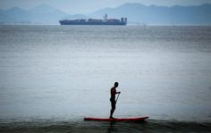 A man paddles on a stand up surfboard off Copacabana beach, in Rio de Janeiro, Brazil, Wednesday March 28, 2012. (AP Photo/Victor R. Caivano)  VICTOR R. CAIVANO - AP