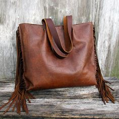 Leather tote bag made in a brown, rustic, cowhide leather. The bag has soft, brown fringe on each side. It is fully lined in beige fabric and has 4, pockets inside. Magnetic snap. Distressed brown leather straps have a 10.5 drop. The bag is 14 across the top and 13 tall with a 3.5 bottom. The bag has been beautifully, saddle stitched by hand by Morgan.