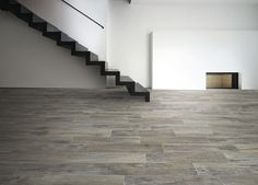 Our Memory Grigio dark oak effect porcelain floor tiles give warmth and starture to this stark modern interior with floating timber stair case. Available from a metre. Wood Effect Porcelain Tiles, Wood Tiles, Porcelain Floor, Tropical Backyard Landscaping, Flagstone Flooring, Tile Flooring, Timber Stair, Rustic Contemporary, Modern Interior