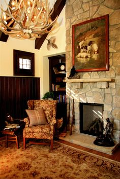 Grand fireplace and antler chandelier in this hunting themed great room