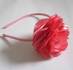 Tiara forrada com fita de cetim, com flor de cetim em tom de rosa.