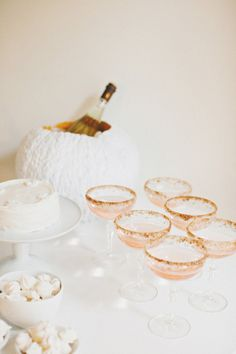 an all white cocktail table complete with pumpkin cooler  Photography by rebeccahansenweddings.com, Design   Styling by stylemepretty.com