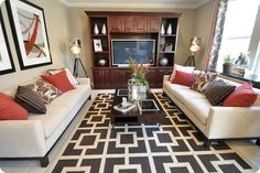 again, red, slate/brown and cream is tricky...the cream couches are nice. Who placed that rug? It's sooo off center!