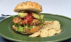 A new twist on an old fan favourite! Homemade chicken burgers rolled in crushed tortilla, smothered in fresh salsa and topped with sliced tomato, avocado and cheese. - Tomato, Egg, Pepper, Burgers, Burger, Main, Bread, Vegetable, Dinner, BBQ, Grilling, Entrée, Mexican, Summer, Chicken, Leafy Green, Avocado