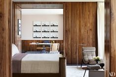 Walnut paneling lends a cozy air to the master bedroom; in the adjoining office, artworks by Robin Rhode hang above a vintage Warren Platner table.