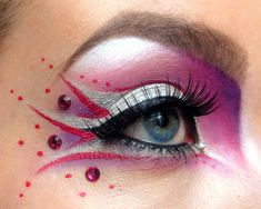 Artistic pink, purple and silver fantasy eye make-up with a trio of purple crystal accents.