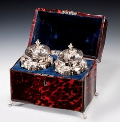 PAIR OF GEORGE III SILVER TEA CADDIES IN A RED TORTOISESHELL CASE  c.1773 // the caddies on cloven feet with embossed festoons, four pilaster supports, two masks, paterae and stiff leaf decoration,  probably by either Samuel Wood or Samuel White, London 1773, together with two George III jockey cap caddy spoons.  The caddies and the jockey caps are engraved with the crests of the Fauconberg/Conyers //  Price: £14500 // - Maria Elena Garcia -  ► www.pinterest.com/megardel/ ◀︎