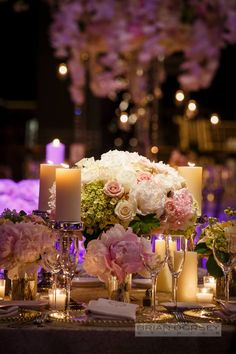 Gorgeous reception table flowers mixed with pillar candles.