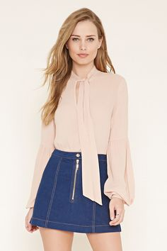 A woven blouse featuring a self-tie V-cutout neckline, shirred accents on the long sleeves, and elasticized cuffs.