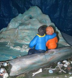"""A couple from Alaska wanted a """"wedding cake"""" that depicted the scene where they became engaged. There were in Alaska looking at a beautiful iceberg while sitting on a driftwood log. og.    The iceberg had a hole in it--quite challenging to recreate with edible materials."""