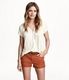 Weite Bluse aus zartem Webstoff. Modell mit kurzem Arm, V-Ausschnitt und Knopfleiste.