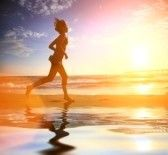 Workout : Woman running by the ocean beach at sunset