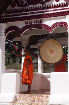 Young monks ring the bels and bang the drums in the early evning. Laos Luang Prabang http://worldtravelfamily.com