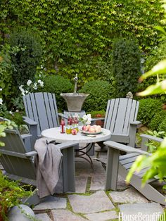 A tiny front yard becomes a pocket paradise, a walled courtyard with graystone pavers, a fountain, Adirondack chairs, and a marble-and-iron table. Design Myra Hoefer