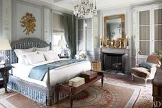 Cabinetry and plasterwork by Féau & Cie and walls painted in a custom-mixed Farrow & Ball gray lend an old-world air to the master bedroom; the Louis XVI–style bed and the mahogany bench are both by Jasper Furniture, the crystal chandelier is by Mathieu Lustrerie, the mirror is 19th-century French, the bed linens are by Nancy Koltes, and the circa-1805 Aubusson is from Beauvais Carpets.