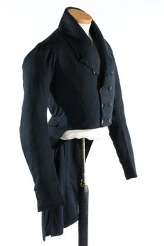 A rare gentleman's navy wool tailcoat, circa 1815. double-breasted with M-notched lapels, kite-shaped rear seaming, black silk covered buttons, sleeve is gathered at the shoulder, high collar, quilting to inside chest and lower neck areas, brown velvet added to line the cuffs, brown chintz lined pockets concealed within the tails