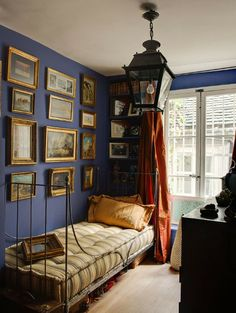 Room of the Day ~ In this French blue guest bedroom a collection of paintings and treasured pieces from travels is displayed above the iron bedstead. Charming lantern and orange drapes. 6.24.2014