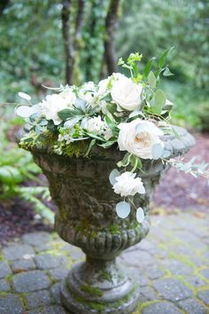 White flowers and eucalyptus leaves in stone planter.