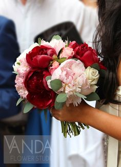 The deep reds and blush pinks look so romantic together in this bridal bouquet. Blush pink Peony, rich red Peony, cream Vendela Rose, and bright pink Rose, with round leaved Eucalyptus.