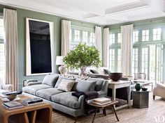 The living room, coated in a green hue by Ralph Lauren Paint, showcases a large Richard Serra etching; Rogers & Goffigon linens were used for the curtains and the upholstery on the custom-made sofas, the cocktail table at left is vintage Frank Gehry, and the jute carpet is by Merida.