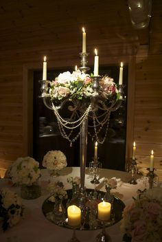 photo of flower arrangment on mirror tiles | Ivory and pink candelabra arrangement, decorated with pearls and ...