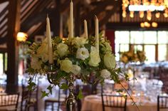 silver candelabras decorated with a ring of white roses and seasonal flowers by spriggs florist
