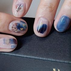 Abstract watercolor nail art design with blues and grays