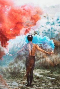 double exposure,from behind,ballet dancer with two colorful smoke bombs dance in nature