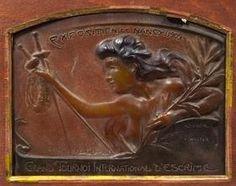 """Almaric WALTER (1870-1959) et Henri BERGE, plaque commémorative en pâte de verre figurant un buste de jeune femme tenant deux fleurets dans une main et une branche de laurier dans l'autre. Porte en partie haute l'inscription : """"Exposition à Nancy 1909"""" et en partie basse """"Grand Tournoi International d'Escrime"""".  Signé """"Daum"""" """"A. Walter"""" et """"Bergé"""". Dimensions : 12,5 cm x 16,5 cm."""