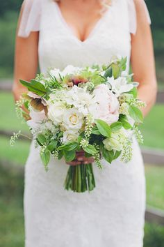 Compact, round, hand-tied, white and blush bouquet with lots of foliage.
