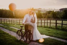 Image by - Lola Rose Photography - Bride & Groom Country portrait with a vintage bicycle & giant balloon - Sottero & Midgely Lace Wedding Dress and Rachel Simpson Shoes for a rustic country wedding in a barn with delicate pastel flowers. Bridesmaids in Navy & Groom in Grey Bartlett and Butcher Suit.