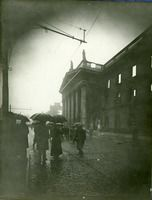 "Post-1916 Rising Dublin General Post Office showing extensive damage: UCD Digital Library, Desmond FitzGerald Photographs ""The photograph has been taken from Nelson's Pillar. Showing the façade of the GPO, with its gutted interior, silhouetted against a dark sky. Members of the public are walking by the GPO in the murky gloom, and a soldier or policeman appears to be on duty."""