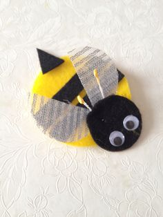 """SWAP I created for Girl Scout Investiture Ceremony. """"New Bee"""" since our girls are new to GS. Bumble Bee made from felt, using sizzix to cut the circles. Antenna made from stamens from the cake decorating aisle. Wings made by first placing clear packing tape over silver ribbon and cutting with a circle die cut. (The tape prevents frayed edges)."""