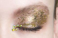 """Per avere un super effetto sparkly stendi l'ombretto dorato ma all'angolo interno aggiungi piccole """"pietre"""" preziose. Completa con il mascara nero."""
