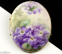 Description: Vintage oval hand painted floral motif porcelain brooch; decorated with purple violets and greenery; brass setting. Designer/Makers Marks, Hallmarks, Tags: Unsigned. Age: Circa 1910's-193