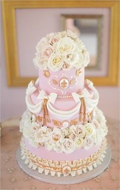 Sweet looking cake romantically decorated with ivory and pale pink roses and fondant drapes