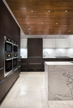 Waterfall edge white marble kitchen island against seamless Pedini cabinetry and Miele appliances. Notice the marble backsplash, seamless edges all the way to the ceiling.