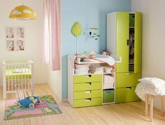 Dormitorio de bebé con un cambiador STUVA y un armario verde y blanco.