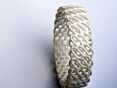 "Diagrid Bracelet by nervoussystem:     ""Inspired by the complex forms of radiolarians, where intricate pattern is integral to structure, these shapes derive from a simulation of spring meshes which form mirrored catenoid surfaces. We created interactive software to morph, twist, and subdivide each design, transforming a simple mesh to a complex patterned structure."""