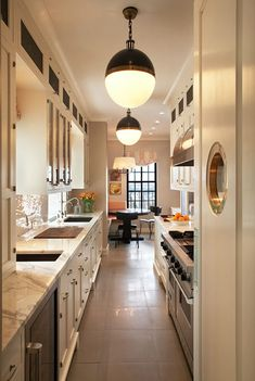 NYC galley kitchen. Marble, creamy white, brass, black accents, and the brass porthole mirror.