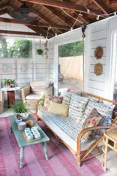 Rustic screened porch with white plank walls, wood plank ceiling and a rustic fan hung on a vintage pulley