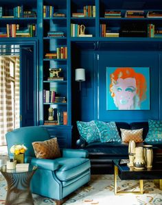 salon éclectique aux nuances de bleu sarcelle et bleu pétrole, une jolie bibliothèque encastrée bleu paon brillant