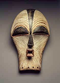 The kifwebe masquerade is a genre shared by the Luba and Songye, indicative of the interaction that has occurred between the two societies. Kifwebe masks represent either male or female beings. Both mask types are characterized by angular and thrusting forms, and in both cases the entire face is covered in patterns of geometric grooves that are uniquely characteristic of these masks. Female masks, such as this one, are distinguished by the predominant use of white clay and the rounded form…