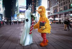 The Statue of Liberty and Big Bird talk as they await people to pose with them for tips in Times Square in New York, March 1, 2014. REUTERS/Carlo Allegri