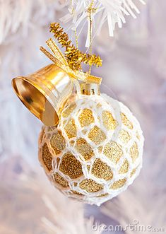 A close up of a beautiful white and gold hand made crochet Xmas tree decoration on white branches.