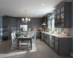 Harper Maple in Greyloft with a contrasting cabinet back in soothing Aegean lifts the spirits in this airy kitchen. Island legs, moldings and timeless drawer pulls add character and personality.