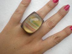 Lindíssimo anel de Fluorita com base de madeira e acabamento em prata. Pedra natural com várias cores. Um verdadeiro arco-íris de pedra!  TRABALHAMOS COM TODOS OS AROS.  DESCONTO DE 10% PARA DEPÓSITOS/TRANSFERÊNCIA BANCÁRIA  Oferecemos certificado de autenticidade da pedra. Favor solicitar. R$149,90